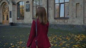 Jong aantrekkelijk wijfje, student die aan de universiteit lopen, vol vertrouwen en gemotiveerd op de achtergrond van andere stock videobeelden