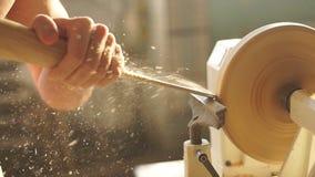 Jong aantrekkelijk wit mannetje, die aan de machine van de houtbewerkingsdraaibank in de timmermansworkshop werken stock footage