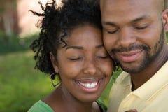 Jong Afrikaans Amerikaans en paar die lachen koesteren stock foto's