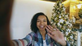 Jong Afrikaans Amerikaans meisje die online gesprek babbelen die smartphonecamera met behulp van thuis dichtbij Kerstboom Stock Fotografie