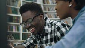 Jong Afrikaans paar die aan de examens in de bibliotheek voorbereidingen treffen stock videobeelden