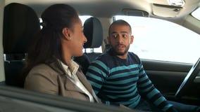 Jong Afrikaans paar die een auto kiezen bij de autosalon stock footage