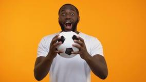Jong Afro-Amerikaans mannetje met voetbalbal die emotioneel voor nationaal team toejuichen stock footage