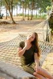 Jong Amerikaans meisje die groene kledingszitting op rieten hangmat met zand en palmen op achtergrond dragen Stock Fotografie