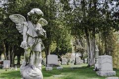 Jong Angel Statue Looking Down Upon een Graf in een Begraafplaats stock afbeeldingen