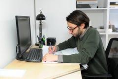 Jong architectenmannetje die in vrijetijdskleding in bureau aan bureau, types die op laptop werken, blauwdrukken op haar bureau l Stock Foto's