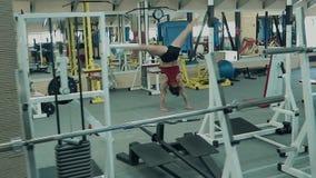 Jong atletisch meisje, atletische bouwstijllooppas langs de gymnastiek, die acrobatische stunts uitvoeren stock video