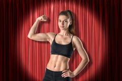 Jong atletisch meisje in zwarte sportkleding die bicepsen op de rode achtergrond van stadiumgordijnen tonen stock fotografie