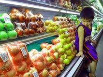 Jong Aziatisch jong geitje binnen een kruidenierswinkel stock afbeeldingen