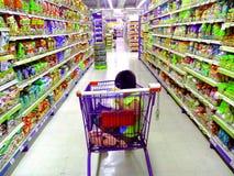 Jong Aziatisch jong geitje die een kruidenierswinkelkar berijden stock fotografie