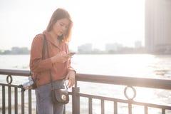 Jong Aziatisch meisje die mobiele telefoon voor onderzoeks interessante plaatsen met behulp van in Bangkok Stock Foto