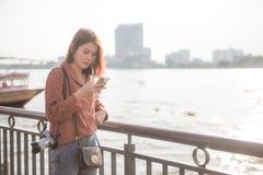Jong Aziatisch meisje die mobiele telefoon voor onderzoeks interessante plaatsen met behulp van in Bangkok royalty-vrije stock foto