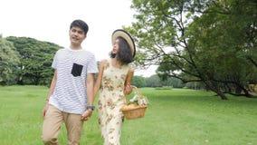 Jong Aziatisch paar die in de lentedag in aard genieten van en op picknick met gelukkige emotie gaan stock video