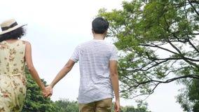 Jong Aziatisch paar die in de lentedag in aard genieten van en op picknick met gelukkige emotie gaan stock videobeelden