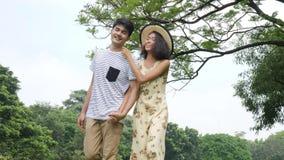 Jong Aziatisch paar die in de lentedag in aard genieten van en op picknick met gelukkige emotie gaan stock footage