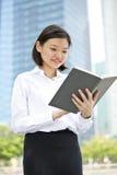 Jong Aziatisch vrouwelijk uitvoerend lezing boek en het glimlachen royalty-vrije stock afbeeldingen