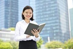 Jong Aziatisch vrouwelijk uitvoerend lezing boek en het glimlachen stock foto