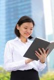 Jong Aziatisch vrouwelijk uitvoerend lezingsboek stock afbeelding