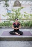 Jong Aziatisch vrouwen drinkwater van glas na oefeningsyoga en meditatie royalty-vrije stock afbeelding