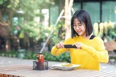 Jong Aziatisch vrouwenvoedsel blogger, vlogger of micro die influencer foto's voor voedselblog nemen die smartphone sociaal netwe stock afbeelding