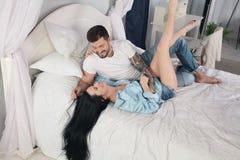 Jong in bed liggen en paar die terwijl het kietelen van elkaar lachen royalty-vrije stock afbeelding
