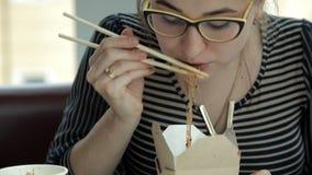 Jong bedrijfsmeisje die Chinese noedels eten bij lunch Zaken, lunch, Chinees voedsel stock footage