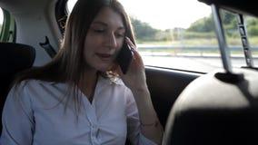 Jong bedrijfsmeisje die naar een taxi gaan en op de telefoon spreken stock footage