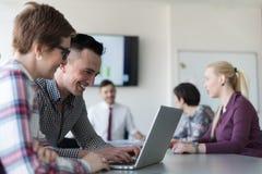 Jong bedrijfspaar die aan laptop, zakenluigroep werken Stock Afbeeldingen