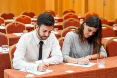 Jong bedrijfspaar die nota's in conferentieruimte nemen Stock Afbeelding