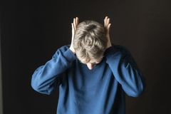 Jong beklemtoond mannetje die zijn oren beschermen tegen hevig irritative lawaai F royalty-vrije stock afbeelding