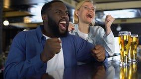 Jong biracial paar dat favoriet sportteam dat in bar online wortel schiet, op gelijke let stock videobeelden