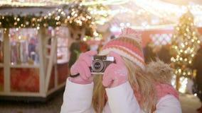 Jong blond glimlachend wijfje die in warme kleren met retro filmcamera een foto op de achtergrond van de winternacht schieten stock videobeelden