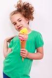 Jong blond golvend meisje met ijshoorntje in de hand Stock Afbeeldingen