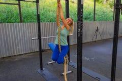 Jong blond meisje die in blauwe beenkappen en groene t-shirt clim glimlachen stock afbeeldingen