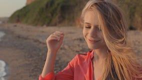 Jong blond meisje in rood met lang haar op stock footage