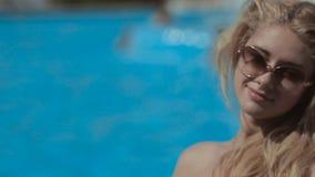 Jong blonde in een bikinizitting dichtbij de pool stock video