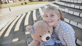 Jong blonde en glimlachend tienermeisje met teddybeerstuk speelgoed in openlucht stock videobeelden