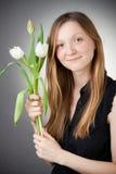 Jong blonde meisje met tulpen Stock Foto