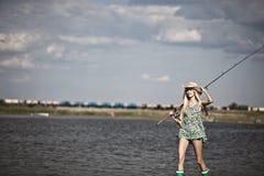 Jong blondemeisje die in meer vissen Stock Foto's