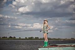 Jong blondemeisje die in meer vissen Stock Foto
