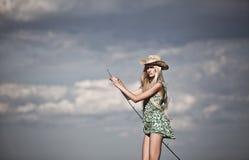 Jong blondemeisje die in meer vissen Royalty-vrije Stock Foto