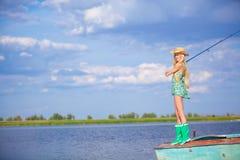 Jong blondemeisje die in meer vissen Stock Afbeelding