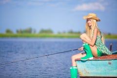 Jong blondemeisje die in meer vissen Royalty-vrije Stock Afbeeldingen