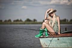 Jong blondemeisje die in meer vissen Stock Afbeeldingen