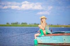 Jong blondemeisje die in meer vissen Royalty-vrije Stock Afbeelding