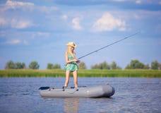 Jong blondemeisje die op boot in meer vissen Royalty-vrije Stock Foto