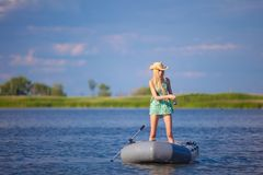 Jong blondemeisje die op boot in meer vissen Stock Foto