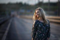 Jong blondemeisje op de weg in het avond zachte licht van de zon stock foto