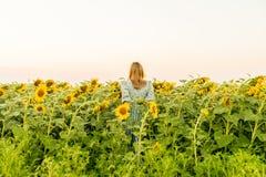 Jong blondemodel op de achtermening van het zonnebloemgebied royalty-vrije stock afbeeldingen