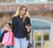 Jong blondewijfje die met roze en rode zakken winkelen die een celtelefoon houden Stock Fotografie